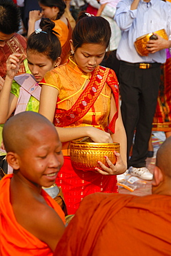 Theravada Buddhism, That Luang Festival, Tak Bat, novice, monks receive alms, Laotian believer with sash and alms bowl, pilgrims giving alms, orange robes, Vientiane, Laos, Southeast Asia, Asia