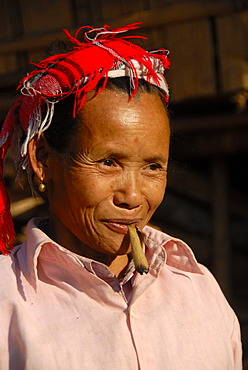 Portrait, woman of the Lao Seng ethnic group smoking a cigar, colorful headscarf, Ban Sopkang, Phou Den Din National Protected Area, Phongsali district and province, Laos, Southeast Asia, Asia