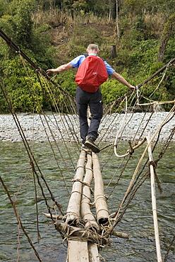 Man crossing a narrow suspension bridge, Kachin State, Myanmar