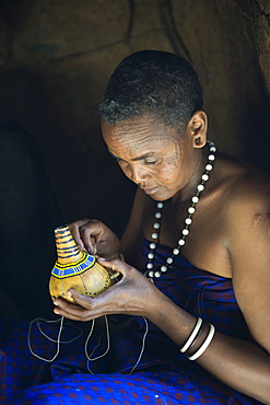 A woman of the Datoga tribe decorating a calabash with glass beads, Lake Eyasi, Tanzania, Africa