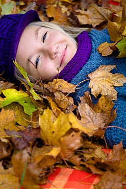 Girl, 13, lying between colourful autumn leaves