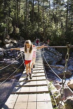 7-year-old girls on suspension bridge over Spasmiata river, Foret de Bonifatu, Corsica, France, Europe