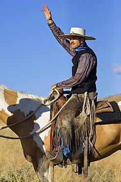 Cowboy sitting on horseback greeting, wildwest, Oregon, USA