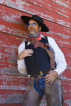 Cowboy leaning on barn wall, wildwest, Oregon, USA