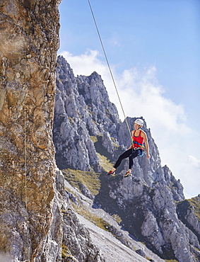 Climber with helmet swinging on climbing rope on rock face, Northern Alps, near Innsbruck, Tyrol, Austria, Europe