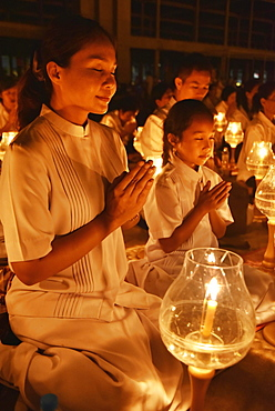 Young woman and child praying, candlelight, Wat Phra Dhammakaya temple, Bangkok, Thailand, Asia