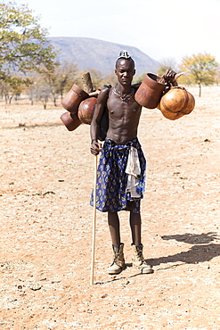 Young Himba man carries food on the cattle drive, Kaokoveld, Namibia, Africa