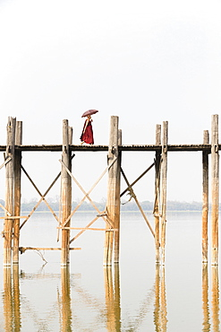 Monk crossing U Bein bridge, Taungthaman Lake, Mandalay region, Myanmar, Asia