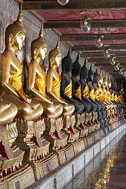 Wall with row of Buddha statues in meditation posture, on decorated pedestals, Phra Rabieng Kot, Wat Suhtat, Royal Temple, Phra Nakhon, Bangkok, Thailand, Asia