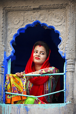 Woman in colorful sari looks out of a window, Jodhphur, Rajasthan, India, Asia