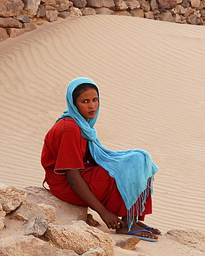 Young woman in colourful clothes sitting on stone, oasis of Al-Ghazali, Sudan, Africa