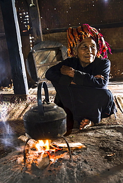 Old woman in the kitchen, kettle on an open fire place in the lodge, mountain tribe or mountain people Pa-O or Pa-Oh or Pao or Black Karen or Taungthu or dew-soo, ethnic minority, near Kalaw, Shan State, Myanmar, Asia