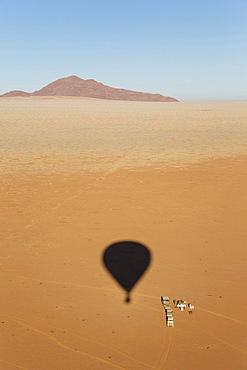Shadow of a hot-air balloon at the intended landing spot in a true desert environment, ground crew prepares an opulent breakfast, photographed from the basket of the balloon, Namib Desert, NamibRand Nature Reserve, Namibia, Africa