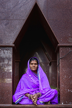 Elderly woman sitting in front of a temple in Pushkar, Rajasthan, India, Asia