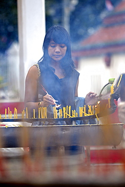 Woman lighting candles outside the Wat Phra Si Rattana Mahathat Temple, Phitsanulok, Northern Thailand, Thailand, Asia