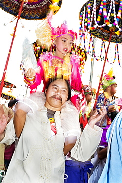 Boy holding a fan, dressed in a bright coloured costume, on the shoulders of male family member, at the annual Poi Sang Long festival, Mae Hong Son, Thailand, Asia