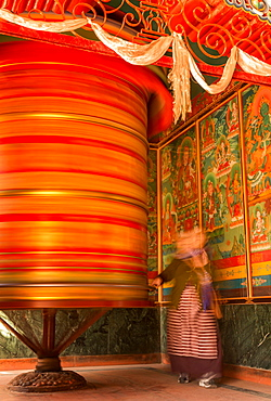 A female devotee spinning a large prayer wheel, Boudhanath, Kathmandu, Kathmandu District, Bagmati Zone, Nepal, Asia
