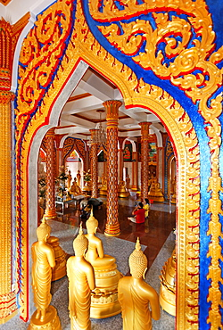 Ornate gate and golden Buddha statues, Wat Chalong temple, Phuket, Thailand, Asia