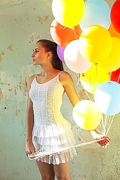 Young woman holding balloons, Germany, Europe