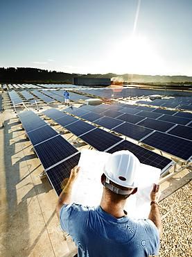 Solar installation technician studying a plan