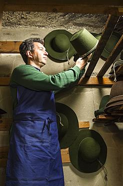 Hatter placing wool felt hat with shaping cord to dry on wooden boards in drying room, hatmaker workshop, Bad Aussee, Styria, Austria, Europe