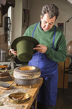 Hatter holding dry wool felt hat over an edge mold, hatmaker workshop, Bad Aussee, Styria, Austria, Europe