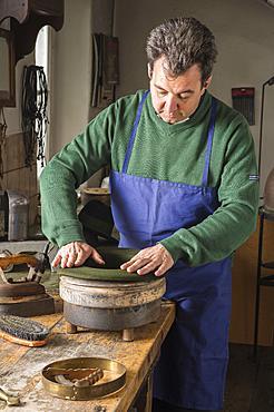 Hatter pushing dry wool felt hat into edge mold, hatmaker workshop, Bad Aussee, Styria, Austria, Europe