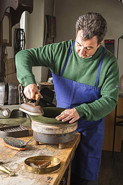 Hatter ironing dry wool felt hat over edge mold, hatmaker workshop, Bad Aussee, Styria, Austria, Europe