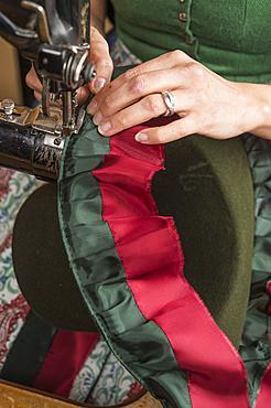 Hands sewing inner lining on a wool felt hat, sewing machine, hatmaker workshop, Bad Aussee, Styria, Austria, Europe