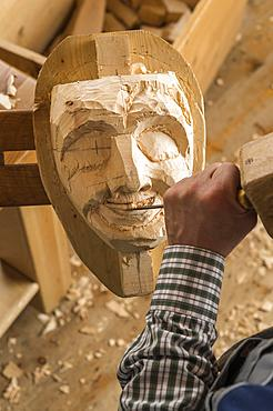 Carving the mouth of a wooden mask using wood carving tools, wooden mask carver, Bad Aussee, Styria, Austria, Europe