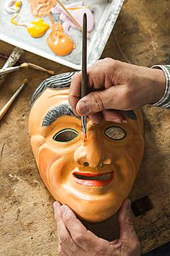 Painting the face of a wooden mask with a paintbrush, on a workbench, wooden mask carver, Bad Aussee, Styria, Austria, Europe