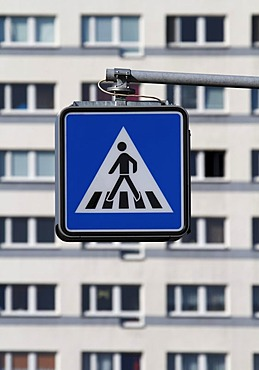 Pedestrian crossing sign in front of apartment buildings