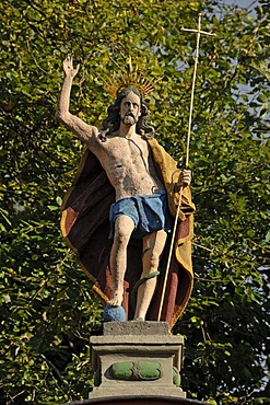 Sculpture of Christ, right hand raised in blessing, holding a crucifix in his left hand, at the entrance to Salvatorkirche Church, Obere Salvatorgasse, Coburg, Upper Franconia, Bavaria, Germany, Europe