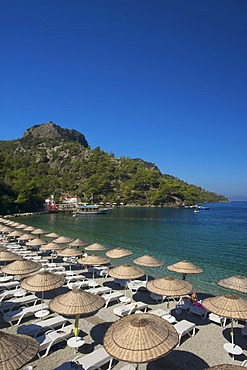 Deck chairs and parasols on the beach of the Hillside Club near Fethiye, Turkish Aegean Coast, Turkey