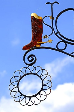 Riding boots with spurs, hanging sign of a shoe shop against a blue sky, Hauptstrasse, Gengenbach, Baden-Wuerttemberg, Germany, Europe