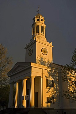 First Parish Church in front of dark thunderstorm clouds, illuminated by the last light of the day, Concord, Massachusetts, USA
