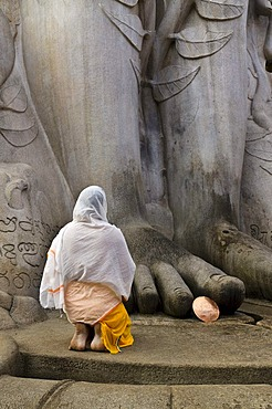 A Jain pilgrim is praying at the feet of the statue of Lord Gomateshwara, the tallest monolithic statue in the world, dedicated to Lord Bahubali, carved out of a single block of granite stone, 18 meters high, 983 AD, Sravanabelagola, Karnataka, India, Asi