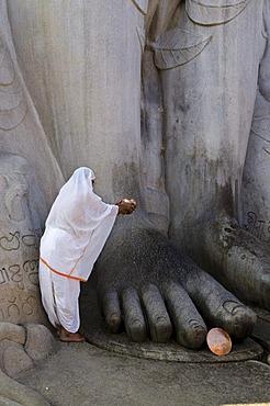 Jain pilgrim is pouring water on the feet of the gigantic statue of Gomateshwara in Sravanabelagola, Karnataka, India, Asia
