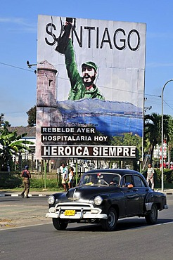 "Vintage car driving in front of revolutionary propaganda poster, ""Santiago siempre heroica"", Spanish for ""Santiago is always heroic"", Plaza de la Revolucion, Santiago de Cuba, Cuba, Caribbean"