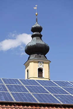 Solar panels on the roof of a house in front of the Church of the Nativity, Frauenried, Irschenberg district, Upper Bavaria, Bavaria, Germany, Europe