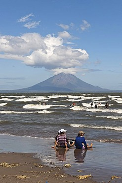People sitting on the shallow shore of Lago de Nicaragua with the volcanic island of Ometepe and the stratovolcano Volcan Concepcion at back, San Jorge, Nicaragua, Central America
