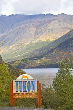 Yukon Territory welcome sign, South Klondike Highway, Indian summer, leaves in fall colours, autumn, Tagish Lake behind, Yukon Territory, Canada