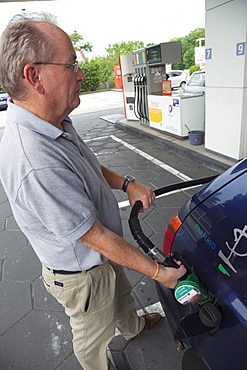 Male driver at petrol station, Munich, Bavaria, Germany, Europe