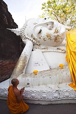 Monk in front of Reclining Buddha statue at Wat Yai Chai Mongkhon, Ayutthaya Historical Park, UNESCO World Heritage Site, Ayutthaya, Thailand, Southeast Asia, Asia