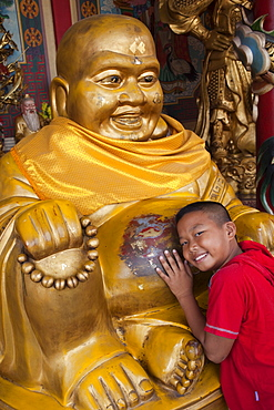 Young Boy with Buddha statue, Chinatown, Bangkok, Thailand, Southeast Asia, Asia