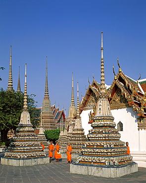 Monks walking past chedis, Wat Pho, Bangkok, Thailand, Southeast Asia, Asia