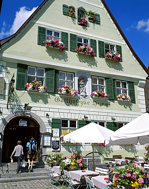 Couple entering typical guesthouse, The Old Town (Altstadt), Dinkelsbuhl, Bavaria, Romantic Road (Romantische Strasse), Germany, Europe