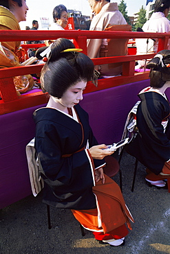 Geisha using mobile phone at Jidai Matsuri Festival held annually in November at Sensoji Temple, Asakusa, Tokyo, Japan, Asia