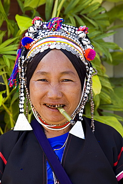 Akha hilltribe woman smoking and wearing traditional costume, Golden Triangle, Thailand, Southeast Asia, Asia
