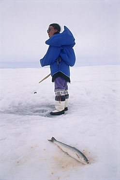 Image of an Eskimo woman ice fishing on a frozen lake in Baffin Canada